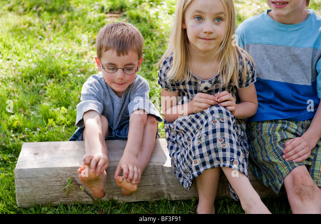 Playful moment with siblings - Stock Image