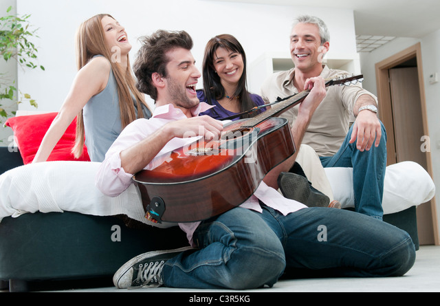 Joyful friends singing and play guitar - Stock Image