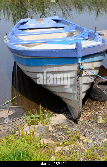 Blue and white rowing boat for hire at Lisloughery Pier,Cong on the shores of Lough Corrib, Ireland. - Stock Image
