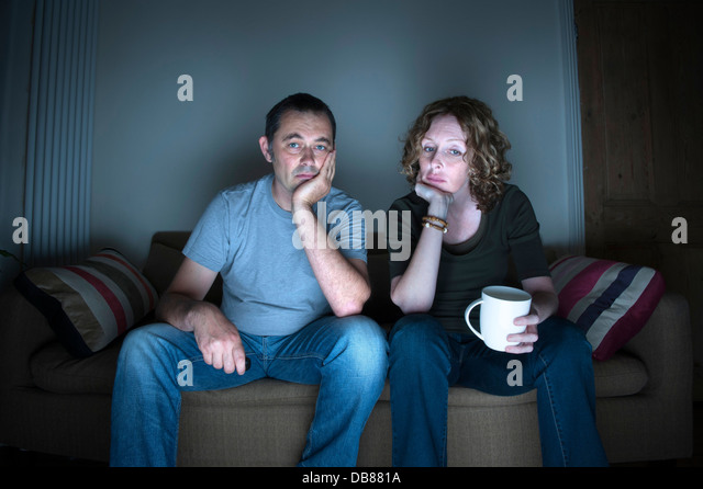 middle aged couple in a relationship watching television bored - Stock Image