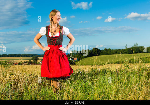 Young Bavarian woman on meadow wearing dirndl and smiling - Stock-Bilder