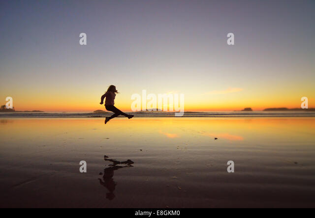 Canada, British Columbia, Alberni-Clayoquot Regional District, Tofino, Young girl jumping on beach - Stock Image