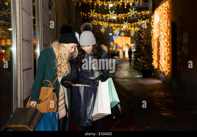 Two mid adult women christmas shopping - Stock Image