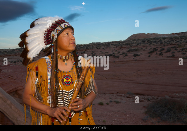 Native American Indian man person with cultural outfit uniform headdress feathers design patterns blue sky nature - Stock Image