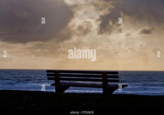 An empty public bench with a dramatic view of a stormy seascape in Bude, Cornwall - Stock Image