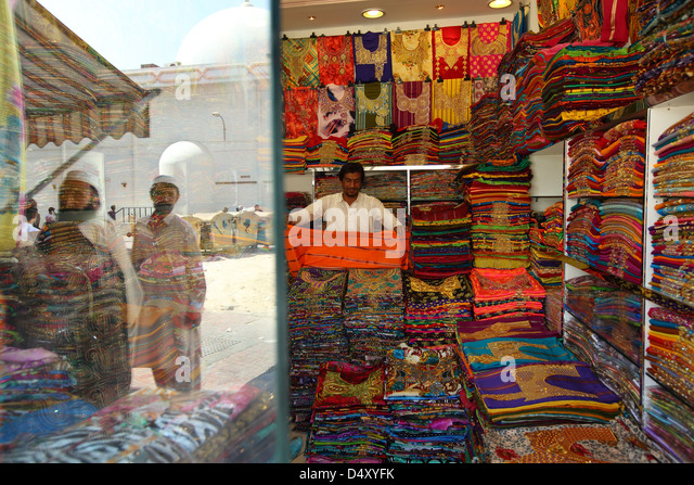 Man folding fabric in textile shop, Dubai, United Arab Emirates - Stock Image
