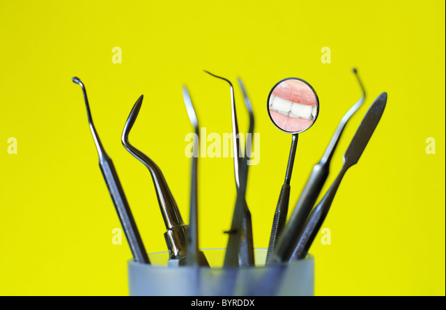 Angled mirror with smile reflection and dental tools in a glass , yellow background - Stock Image