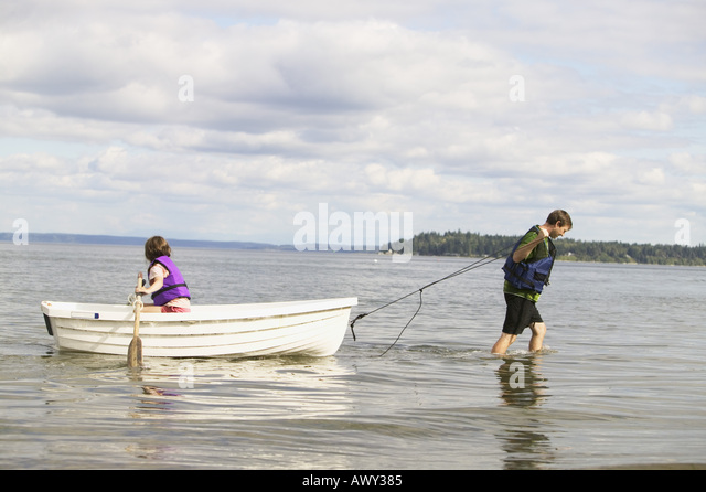 Dad and daughter using a rowboat - Stock Image