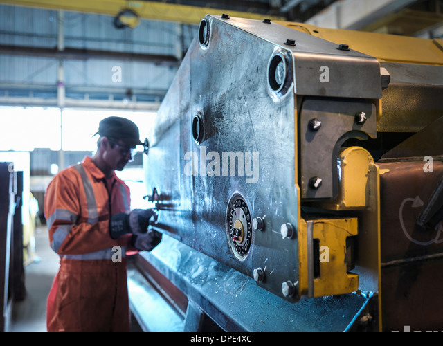 Engineer inspecting work in factory - Stock Image
