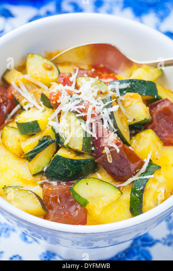 A Close Up View of a Bowl of Polenta with Zucchini Tomato Sauce - Stock Image