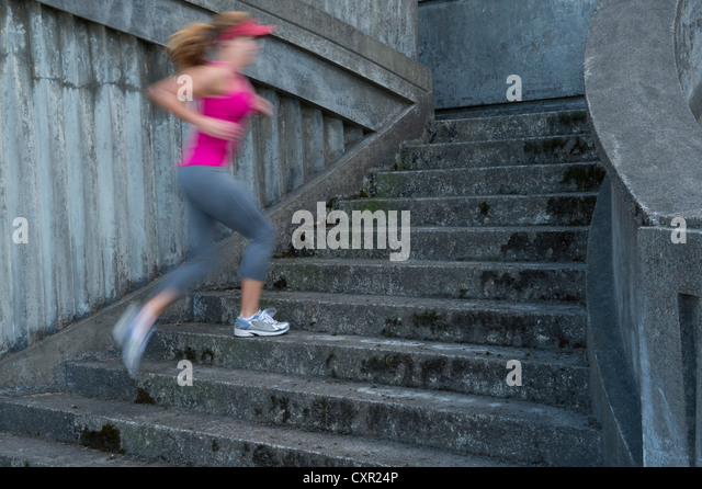 Young woman running up stairs, motion blur - Stock Image