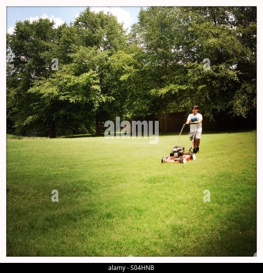 Boy cutting grass - Stock Image