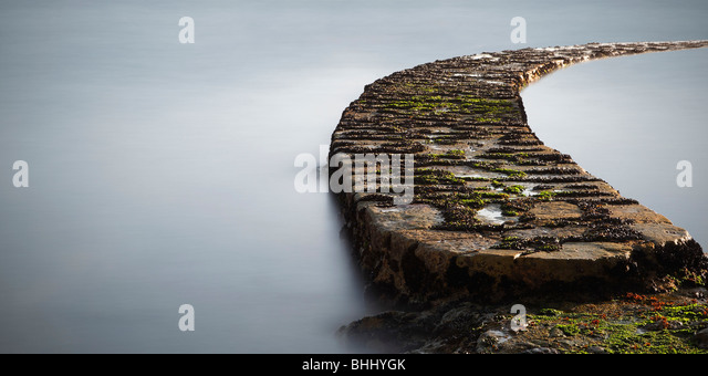 Stone path out to sea - Stock Image