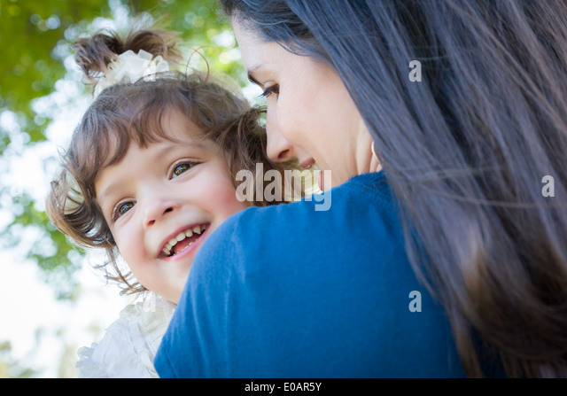 Young Mother Holding Cute Laughing Baby Girl Outdoors in the Park. - Stock Image