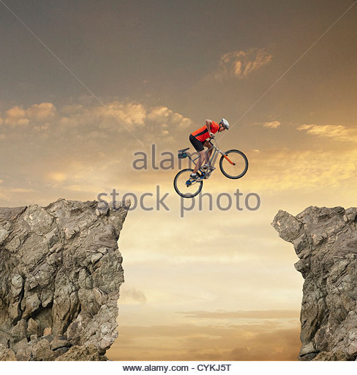 Mixed race bicyclist jumping over canyon - Stock Image
