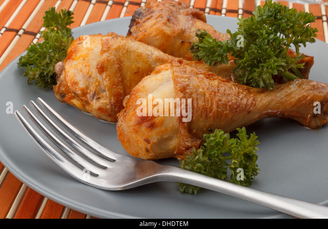 grilled chicken legs served with parsley sitting on a gray plate next to a fork - Stock Image