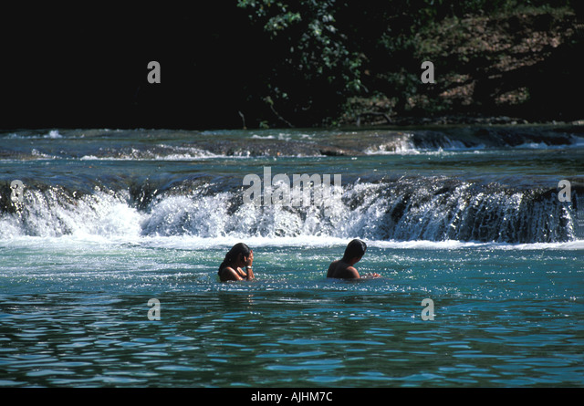 Belize couple standing swimming in river beside waterfalls rapids tropical - Stock Image