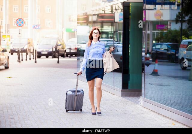 Businesswoman with wheeled suitcase, Warsaw, Poland - Stock Image