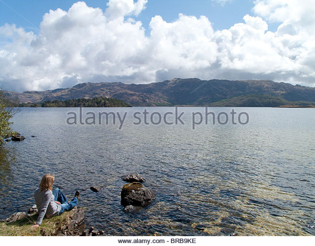 Woman sitting on shore of tranquil lake with land in background - Stock Image