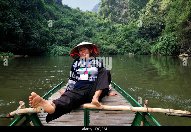 Woman rowing with feet, near Ninh Binh, on the way along the river to the caves of Trung Anh, dry Halong Bay, Vietnam - Stock Image