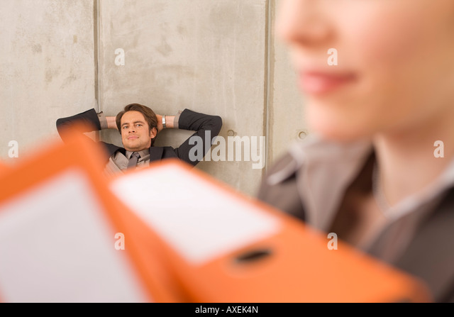 Businesswoman carrying folders, businessman in the background - Stock-Bilder