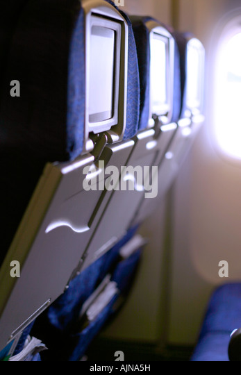 Back of the commercial airplane seats with entertaining system. - Stock Image