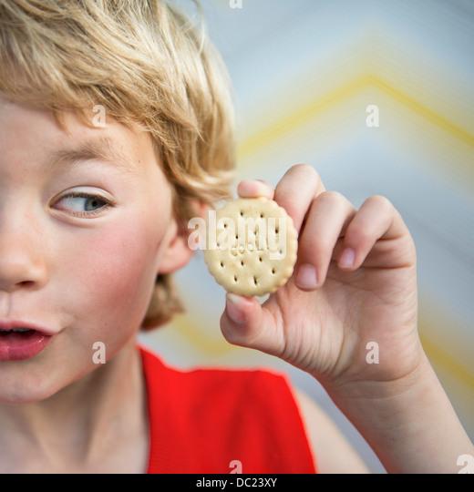 Boy holding cool biscuit - Stock-Bilder