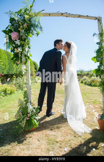 A bride and groom steal a kiss on their wedding day - Stock Image
