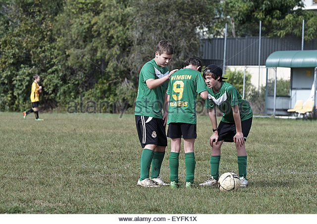 two team mates console an injured player, during a weekend soccer match, at the goonellabah soccer club - Stock Image