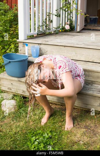 Sweden, Stockholm Archipelago, Grasko, Girl (12-13) washing hair outside - Stock Image