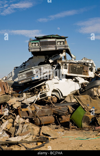 Stack of cars automobiles vehicles in salvage recycling yard against blue sky Barstow California USA - Stock Image