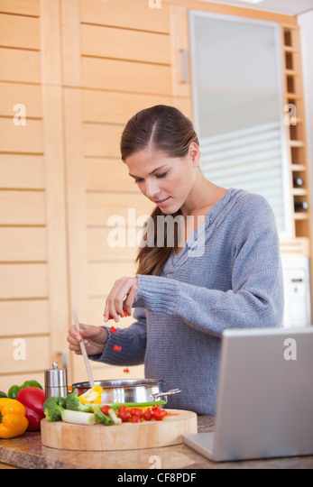 Woman adding carrot pieces to her stew - Stock Image
