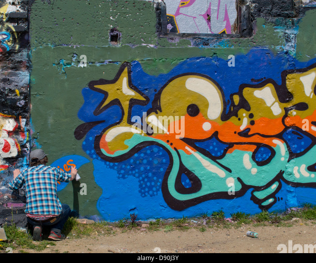Graffiti artist at work on a wall in Brighton - Stock Image