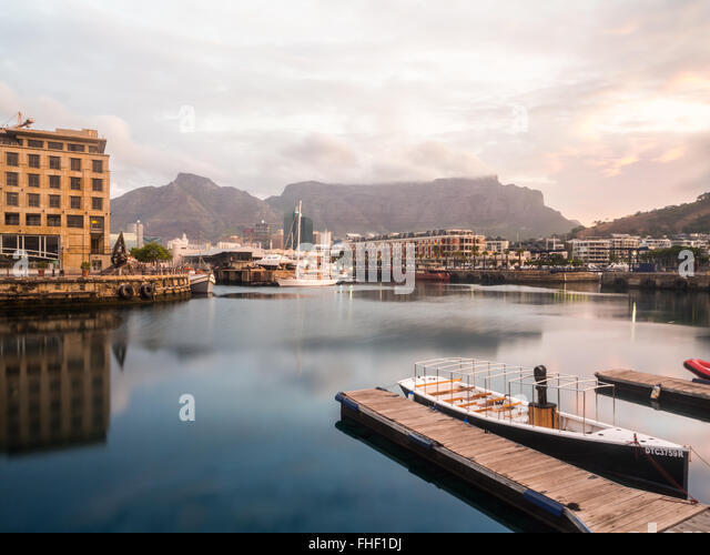 Waterfront in Cape Town, South Africa, overlooked by Table Mountain at sunset. - Stock Image