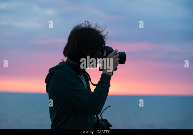A silhouette of a professional photographer man taking a photograph with a DSLR camera against a sunset - Stock Image