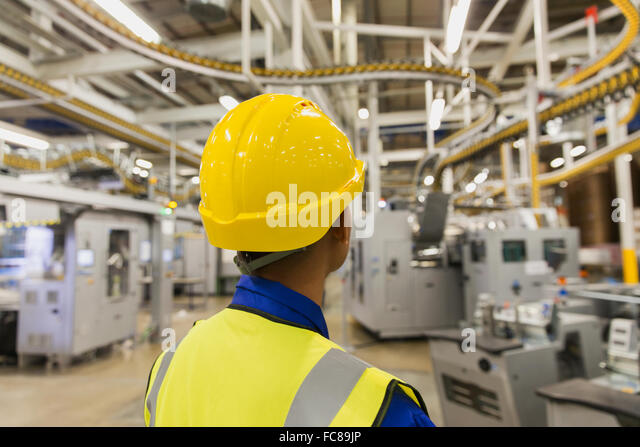 Worker in hard-hat watching printing press conveyor belts and machinery in printing plant - Stock Image