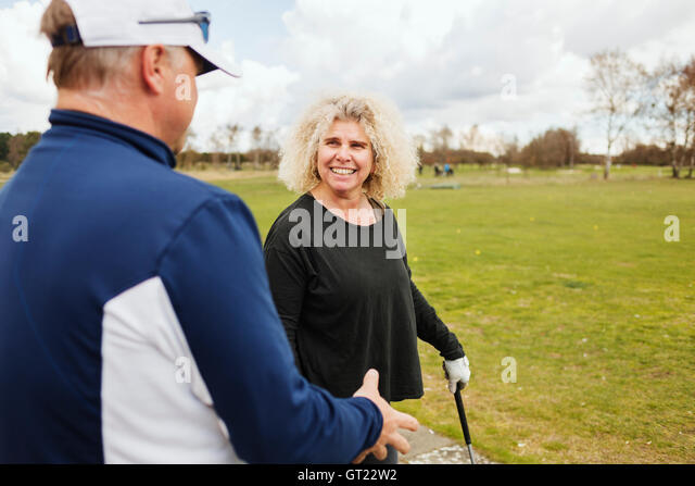 Happy friends talking while playing golf - Stock-Bilder