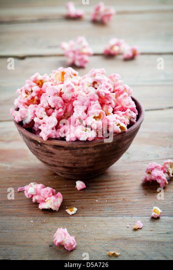 Pink chocolate pop corn in brown bowl - Stock Image