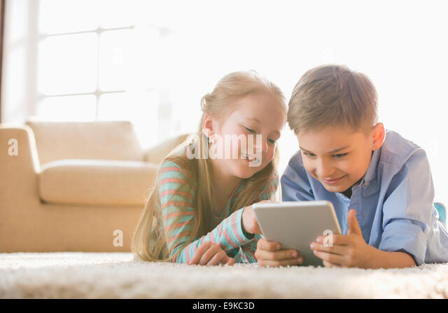 Brother and sister using digital tablet on floor at home - Stock-Bilder