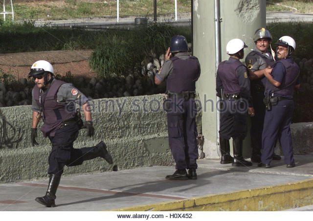 Venezuelan police look for alleged gunmen in Caracas, January 9, 2003.  Shots were fired at a group of people protesting - Stock Image