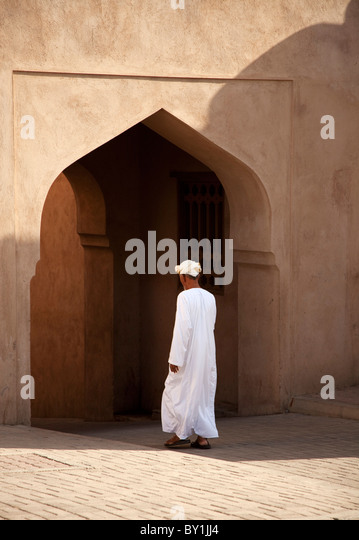 Oman, Nizwa. A local man wanders through an archway in Nizwa. - Stock Image