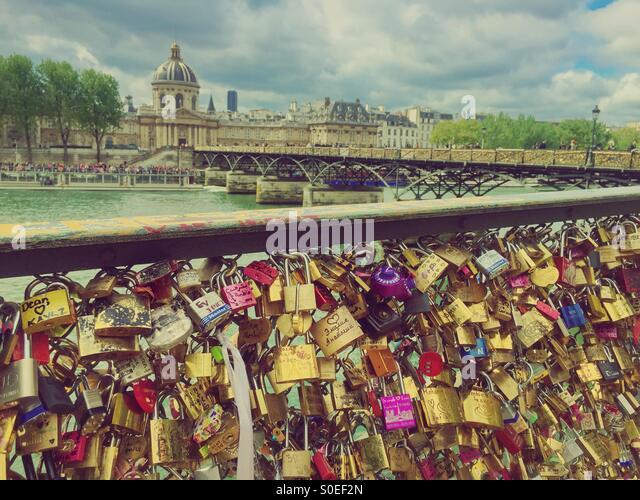 Pont des Arts or Passerelle des Arts, a pedestrian bridge in Paris, France with side panels covered in padlocks - Stock Image