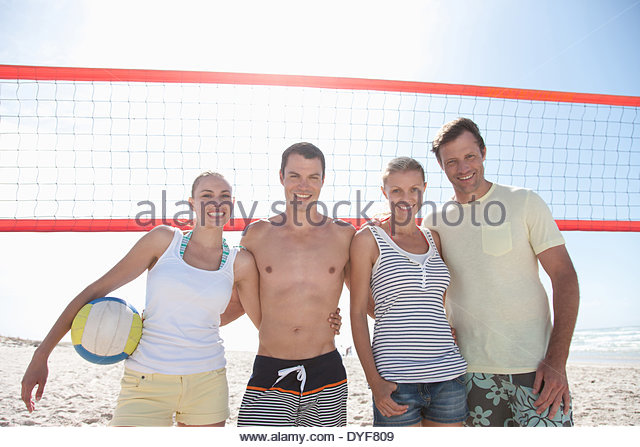 Friends on beach volleyball court - Stock Image