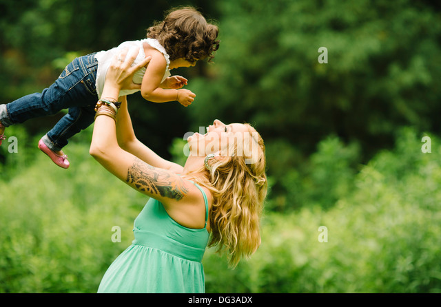 Pregnant Mother Lifting Up Child Over Head - Stock Image