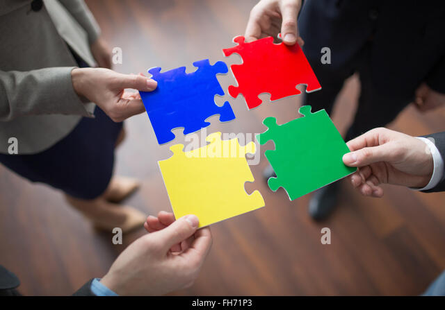 Multi-color puzzle pieces held by co-workers - Stock Image