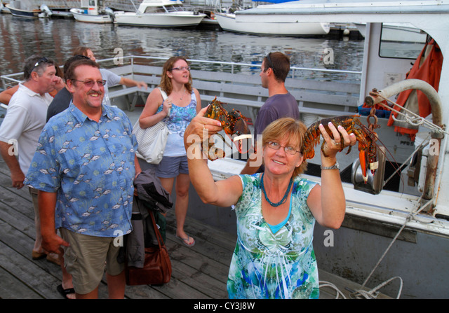 Portland Maine Historic Old Port District Long Wharf Lucky Catch Cruises lobstering excursion man woman couple holding - Stock Image