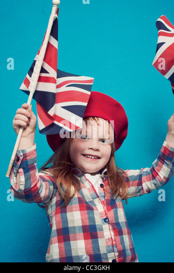 A young girl waving two British flags - Stock-Bilder