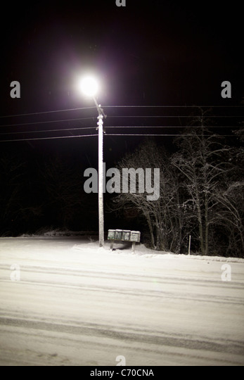 Streetlight over snowy road at night - Stock Image