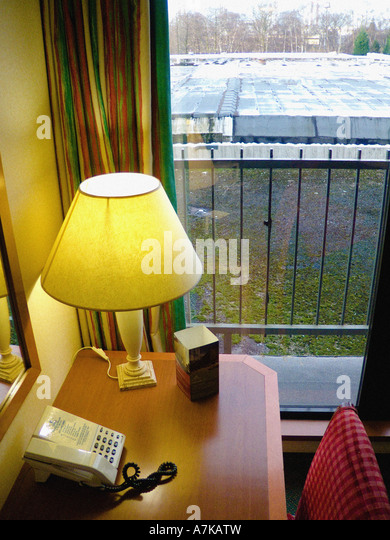 desk with phone and lamp in uk hotel boring dull view out of window in background - Stock-Bilder