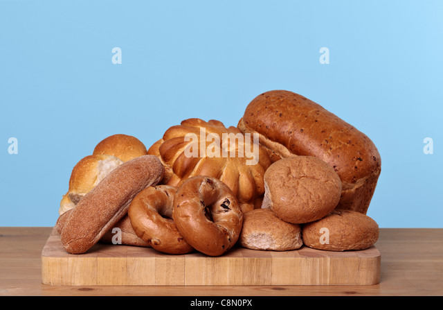 Photo of various types of bread loaves and rolls on a wooden board. - Stock Image